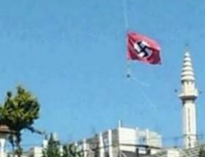 Des centaines d'habitants au Sud du Mont Hébron, Kiryat Arba, Hebron et Gush Etzion, qui étaient en route, en voiture, vers Jérusalem ce lundi matin, ont repéré à leur plus grande surprise une croix gammée (swastika) sur un drapeau suspendu sur les hauteurs de la banlieue de l'implantation arabe de Beit Ummar.