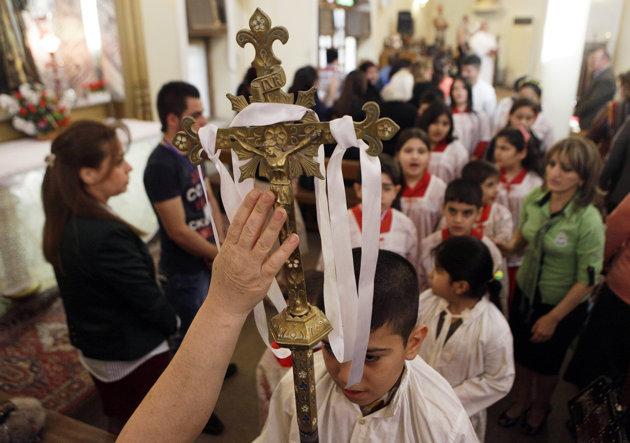 Un fidèle touche le crucifix de la main au cours de la messe de Pâques en l'église de la Vierge Marie, l'église Chaldéenne de Bagdad – Irak – le dimanche 31 mars 2013. L'église chaldéenne est un rite oriental affilié à l'église Romaine Catholique.