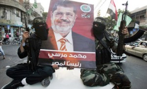 Hamas militants hold a poster depicting Mohamed Morsy of the Muslim Brotherhood as they celebrate in the street in Gaza City after he was declared Egypt's first democratic president June 24, 2012. Morsy's win was hailed by Hamas, the Islamist group governing Gaza and which is locked in a power-struggle with the West Bank-based, U.S.-backed Palestinian Authority of President Mahmoud Abbas. REUTERS/Mohammed Salem (GAZA - Tags: POLITICS ELECTIONS TPX IMAGES OF THE DAY MILITARY)