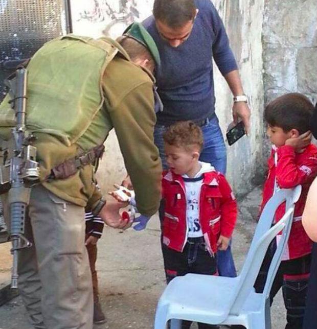 Soldat israélien soignant un enfant palestinien à Hébron
